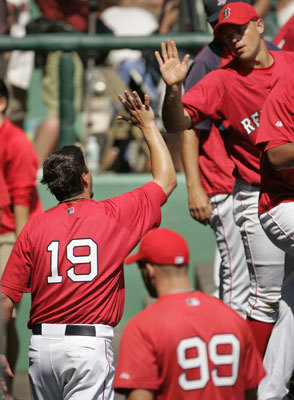 Josh Beckett (left) exchanges a high five with teammate pitcher Michael Bowden (top right) in the dugout moments before a spring training exhibition game against Boston College.