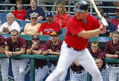 As J.D. Drew bats in the second inning, Boston College player John Leonard (second from left) from Hanover, records the action from the visitor's dugout with a Flip video camera.