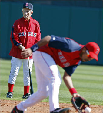 During Red Sox infield practice, Boston legend Johnny Pesky was in the outfield, behind shortstop Julio Lugo, as he fielded a ground ball.