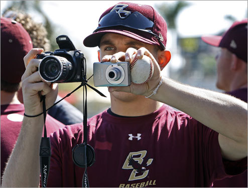 Boston College student manager David Hasebroock juggles two cameras and a baseball as he shoots photos of Boston College players posing with Red Sox players.
