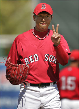 Hideki Okajima signals to the catcher while warming up for the fourth inning of Thursday's spring training game.