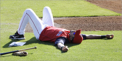 Shortstop Julio Lugo takes a break in the grass before Boston's March 6 game against the Marlins. The Red Sox beat Florida, 5-3.