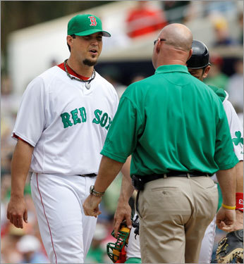 Josh Beckett talked with trainer Paul Lessard after he fielded a bunt. Beckett said after the game that suffered 'just a cut' on the play.