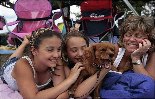 Lacie, a nine-month-old Cavachon puppy, was the center of attention on the Esplanade on July 4, 2007. Left to right, Kristianna Landry, 13, Kelsey Harris, 13, and Kelsey's mother, Deb Daigle, played with Lacie.