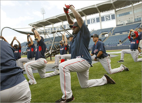 The team stretches during warmups before the game.