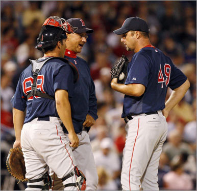 Sox manager Terry Francona (center) talks to pitcher Tim Wakefield (right) and catcher George Kottaras before taking Wakefield out of the game in the sixth inning of the 7-1 loss.