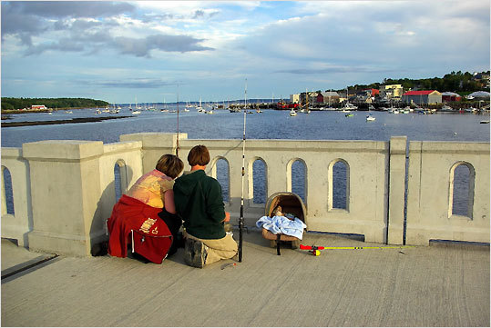 A couple prepare to cast for flounder from the Belfast footbridge built on the remains of the old Route 1 bridge.