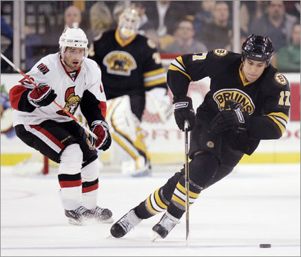 Milan Lucic (right) skates up ice in front of the Ottawa Senators' Mike Fisher in the second period.