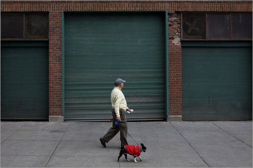 Fenway resident Brendan Flaherty and his dog, Sam, walk by Fenway Park after the Sox postponed their home opener due to rain. Flaherty, who had not heard the game was postponed at the time, had tickets for the game and said he would be back tomorrow.