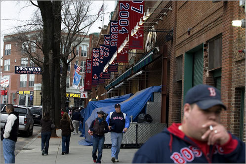 Fans walk outside of Fenway Park after the Sox announced the Monday's cancellation.