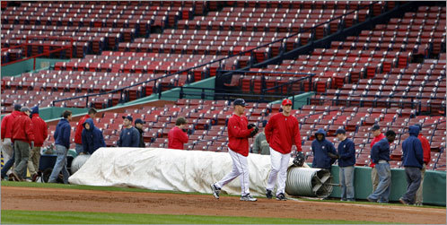 Sox players J.D. Drew (left) and Jason Bay are shown while the Fenway Park grounds crew stand near the rain tarp.