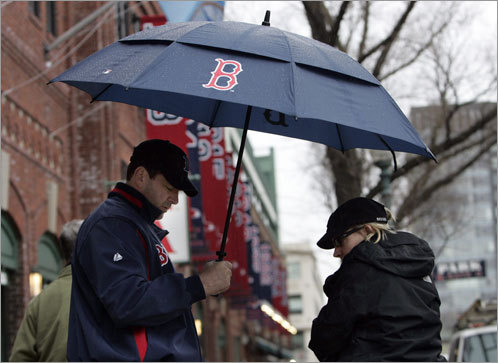 A pair of Sox fans leave Fenway after hearing that Monday's home opener against the Tampa Bay Rays was postponed due to rain. The first game of the Sox season was rescheduled for 4:06 p.m. on Tuesday.