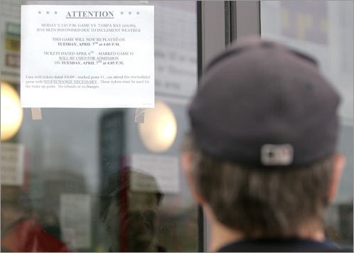 A Sox fan arriving at Fenway reads a sign announcing that the home opener has been postponed.