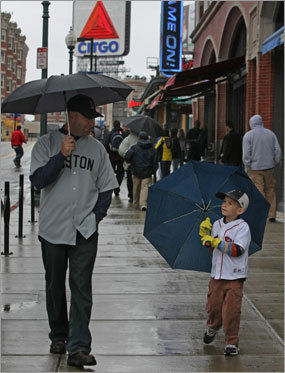 Ronn Potter from California, who use to live in Belmont, walks by Fenway with his 6-year-old son Max. The pair hopes to make it to the rescheduled game tomorrow.