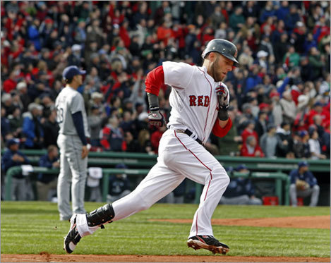 Sox second baseman Dustin Pedroia rounds first base after hitting a solo home run in the bottom of the first inning. Behind him, Tampa Bay pitcher James Shields watches the ball sail over the Green Monster.