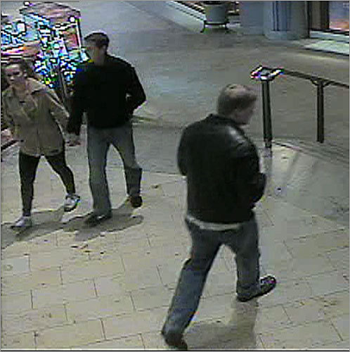 Police also released surveillance photos from the nearby Copley Place Mall. In this photo, the person of interest walks by a couple.