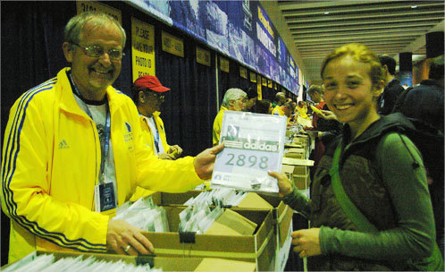 Sumner Fletcher, 23, of Uxbridge, Mass., picked up her number from volunteer Neil Svendson (left). Fletcher , who qualified through running the Bay State Marathon in Lowell, is running her second Boston Marathon.