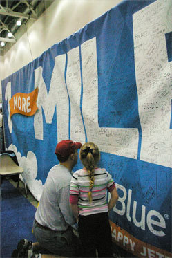 A runner signs a large good luck banner at the JetBlue Airways booth