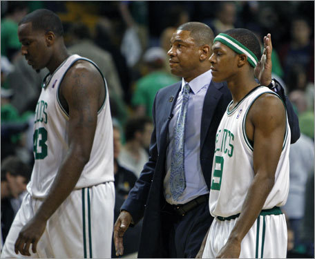 Celtics coach Doc Rivers (center) patted Rajon Rondo on the head as they head to the locker room after the loss. Kendrick Perkins is at left.