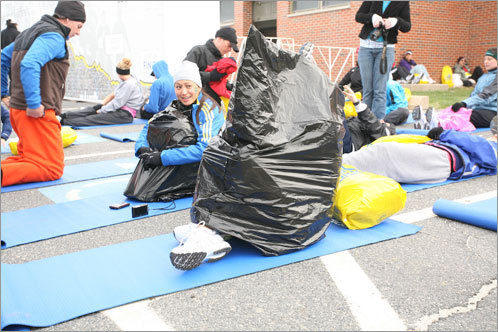 A runner keeps warm inside a garbage bag outside Hopkinton High School.