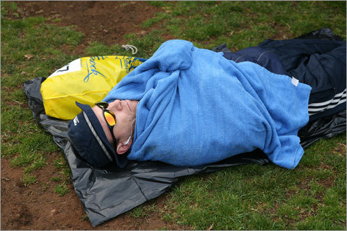 A runner relaxes in the grass before the start of the race.