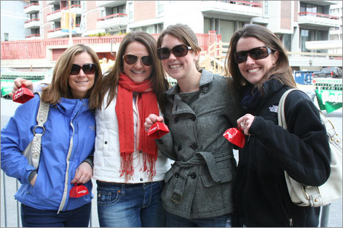 Tricia Smith, Emily Webering, Kate Williams and Natalie Klees, all of Boston, gathered in Kenmore Square to ring cowbells and cheer on Williams's friend Meg Kimball, and Meg's fiancee, David.