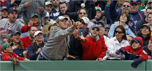 Three fans along the front row tried for a seventh-inning foul ball off the bat of Mike Lowell.