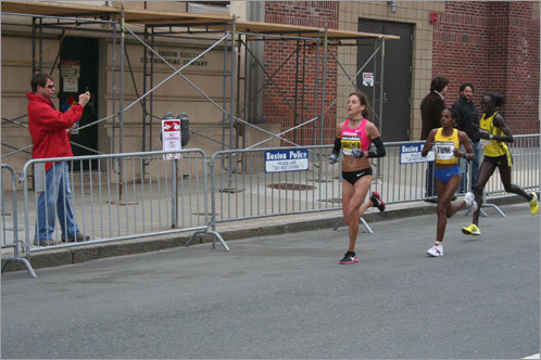 A spectator snapped a cell phone photo of the first three women to run into Kenmore Square, including leader Kara Goucher.