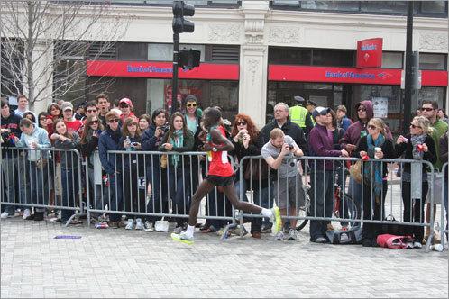 A runner speeds past the camera-wielding spectators.