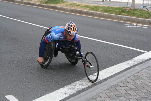 A wheelchair competitor zips into Kenmore Square.