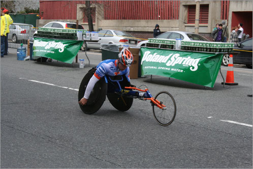 A wheelchair competitor keeps his wheels moving at a rapid pace as he arrives in Kenmore Square.