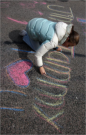 Renee McGowan, 12, of Virginia, chalks encouragement for her parents Jim and Tammy McGowan, who were running the marathon, at the Heartbreak Hill section of Commonwealth Avenue in Newton.