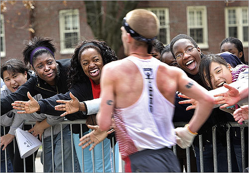 Wellesley students offer a friendly hand and lots of encouragement as runners pass the college.