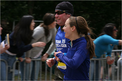 A pair of runners smile as they pass through Wellesley.