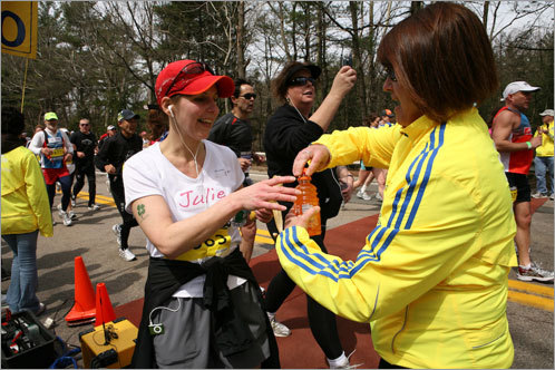 A runner stops to grab a drink from a marathon volunteer.