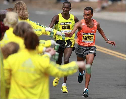 Merga, right, took a drink at a water station in Newton with second-place finisher Daniel Rono following closely behind after completing 18 miles of the 26.2 miles.
