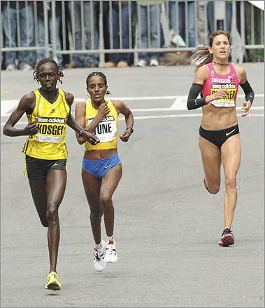 Kosgei, left, defending champion Dire Tune, of Ethiopia and Kara Goucher, of the US, right, made their way to the finish.