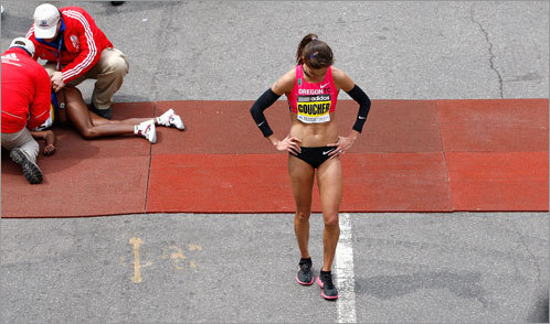 Goucher shows her disappointment after fading during the final stretch of the race, while medical personnel help the collapsed Tune.