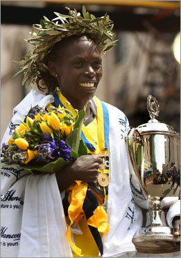Kosgei accepts her trophy as she is honored as the women's champion.