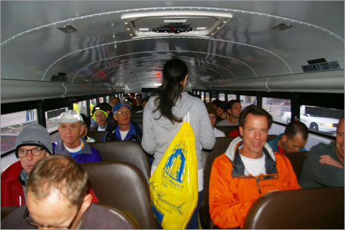A runner looks to find a seat on a packed bus.