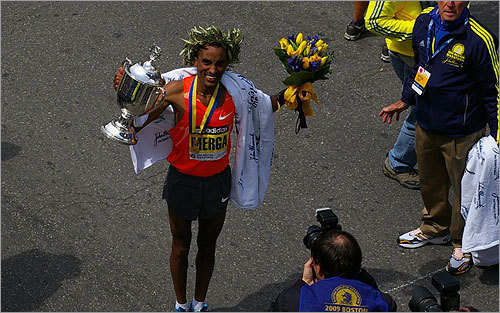 Deriba Merga celebrates with his trophy and victor's wreath after winning the men's race.