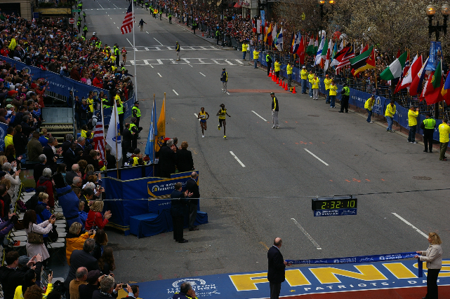 Tune and Kosgei approach the finish line on Boylston Street with Goucher in third place just behind them.