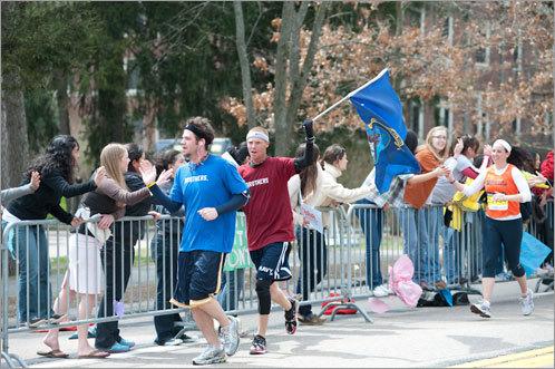 Runners slap hands with spectators.