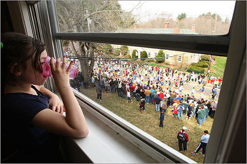 Eight-year-old Eleina Wade watches the elite runners leave the starting line from a window at the International Consulting Services Group office building in her hometown of Hopkinton.