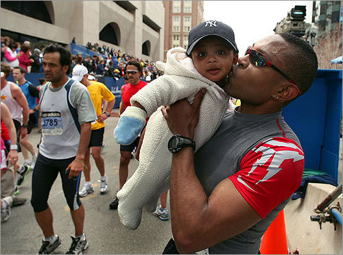 Dwane Morgan from Newton kisses his 6-month-old son Dwane Jr. at the finish line.