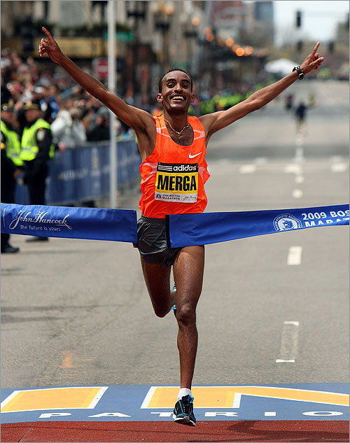 Deriba Merga of Ethiopia raises his arms in triumph as he crosses the finish line to win the men's race in 2:08:42