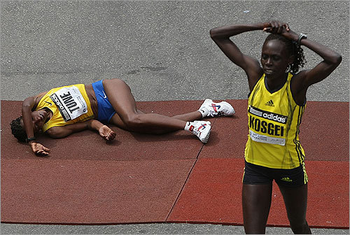 Tune (left) fell to the ground at the finish line, and was tended to by medical staff. Kosgei finished in 2:32:16.