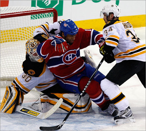 Canadiens right wing Georges Laraque (17) stumbles into goaltender Tim Thomas (30) after taking a hit from Bruins defenseman Shane Hnidy (34).