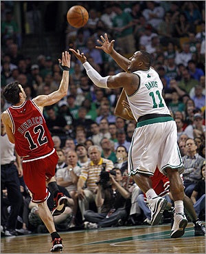 Glen Davis (right) hauls in a length-of-the-court bomb from Kendrick Perkins as he beats guard Kirk Hinrich in the final second of the third quarter.
