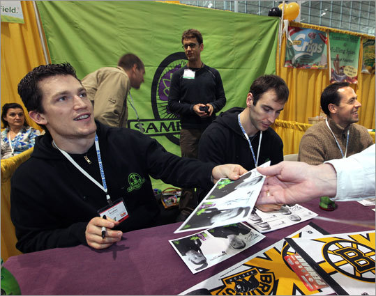 Ference (left), alongside teammates Zdeno Chara (center) and Marco Sturm (right), sign autographs for fans attending the Boston Produce and Floral Show at the Boston Convention Center in April.